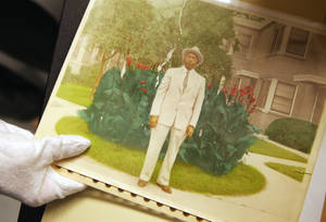 A photo archivist holds a tinted photograph on a table in the photo archive room at the Oklahoma History Center in January. The Center has hundreds of thousands of photographs and documents related to black history.